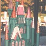 "This was created for a large Golf Tournament at Piper's Landing in Stuart FL in 1995 with a ""Wizard of Oz"" theme.  the castle was made out of a styrene material and  would light up on the inside, covered in fondant, the actual cake was large sheet cakes covered in clouds below the castle."